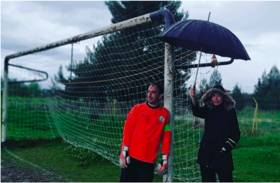 Photo of Greek Mum holding umbrella at son's football game goes viral